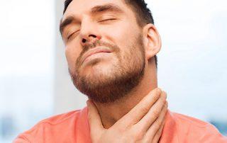 man holding throat in discomfort